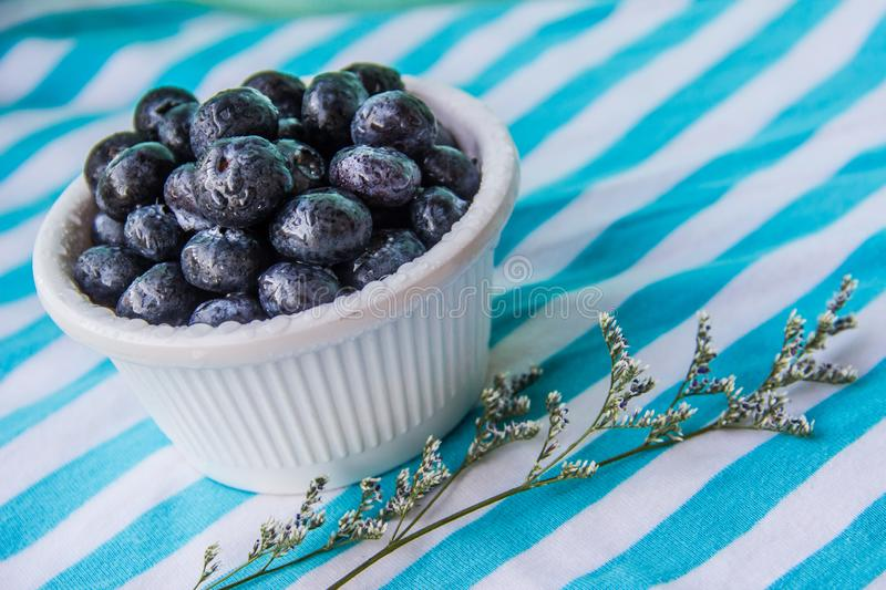 A Cup Of Juicy Blueberries At A Bright Blue Stripy Background. A white cup with juicy blueberries at the stripy blue-and-white background royalty free stock photos