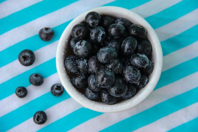 A Cup Of Juicy Blueberries At A Bright Blue Stripy Background. A white cup with juicy blueberries at the stripy blue-and-white background royalty free stock photo