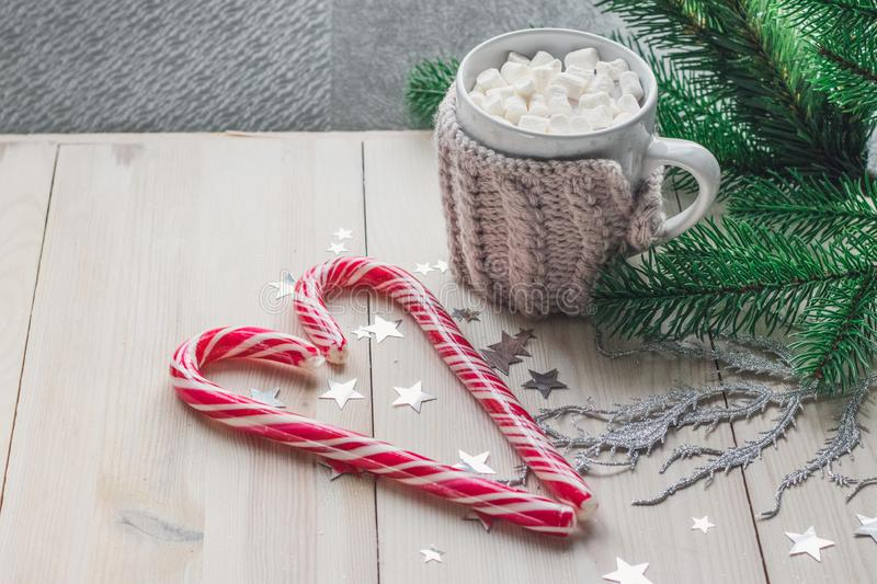 Cup in a knitted jacket with two red caramel Christmas candies that lie in the shape of a heart on a white wooden background stock image