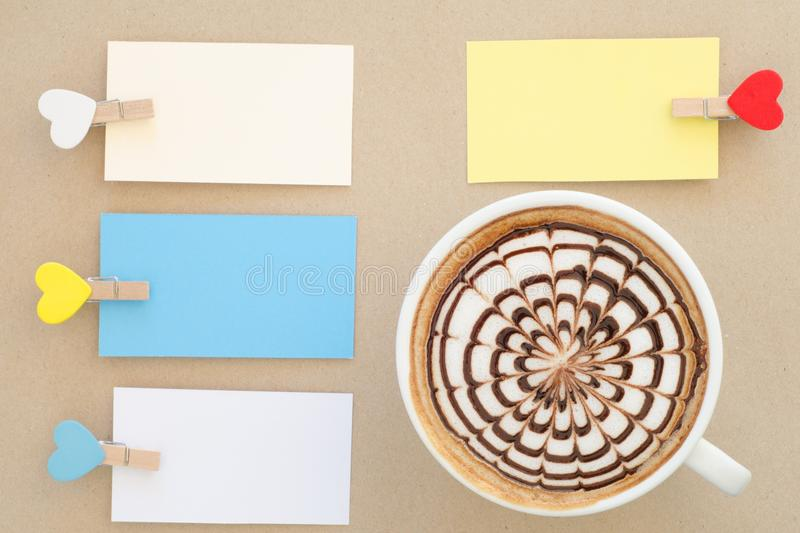 A cup of latte art and clip note. On brown paper background royalty free stock images