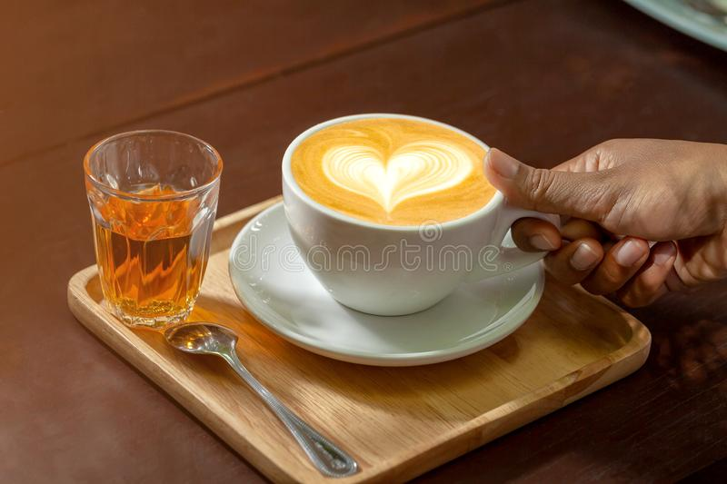 Cup of latte coffee in female hand on white plate on brown wooden table royalty free stock photos