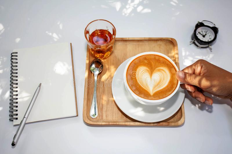 Cup of latte coffee in female hand on white plate.select focus. stock images