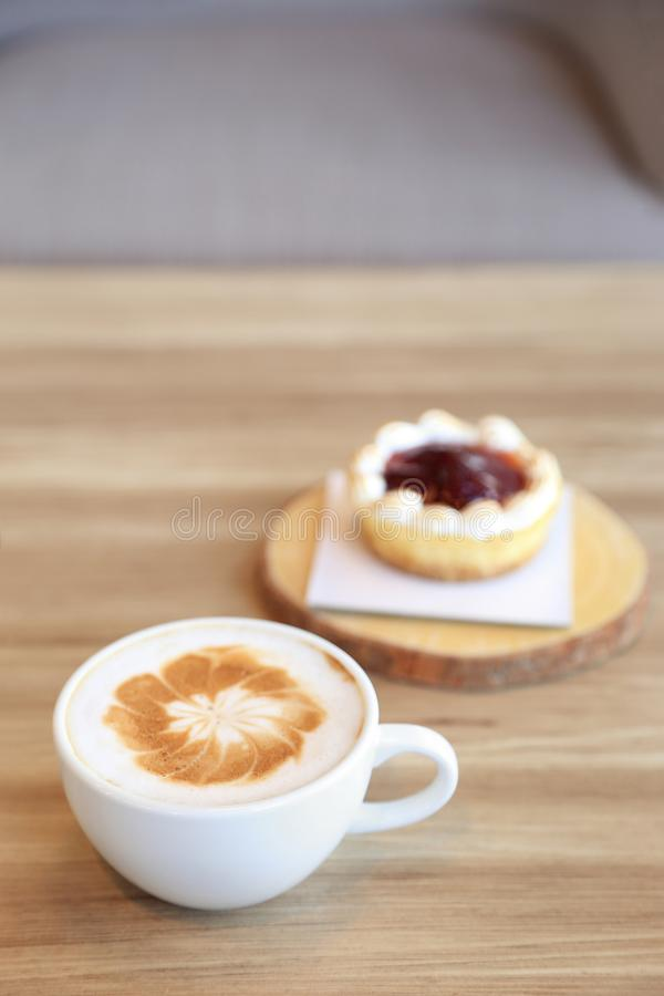 Cup of latte coffee with latte art and strawberry tart pie on wo. Oden background royalty free stock photography