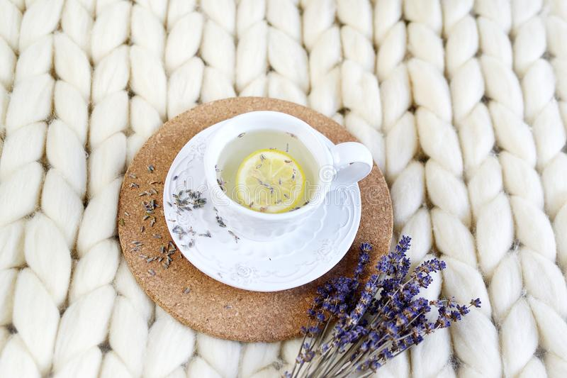 Cup with lavender tea, citrus and honey, croissant, white pastel giant knit blanket. Bedroom, flowers tulips, spring, woman day, morning concept stock images