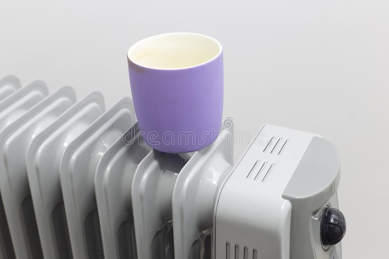 The cup lays on oil heater for heating. The cup lays on oil heater for heating royalty free stock images