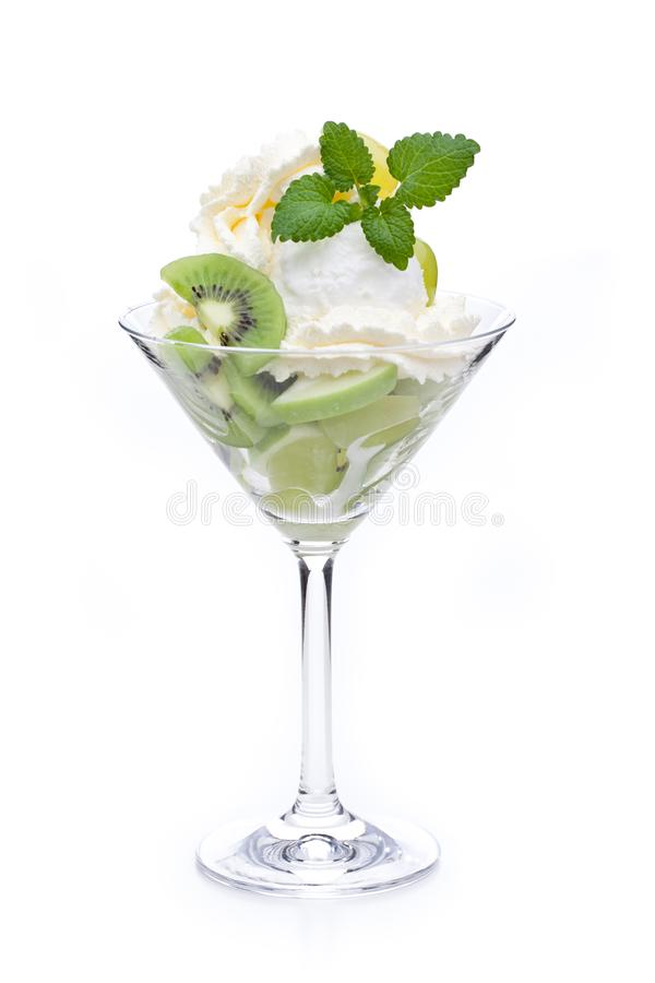 A cup of lemon ice cream decorated with kiwis and mint leaves stock images
