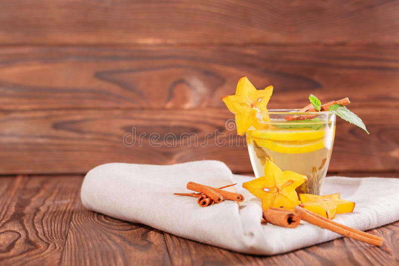 Cup of lemon tea with mint on a wooden background. Sweet, hot and healthy green tea. Tea with carambola and cinnamon. Copy space. stock images