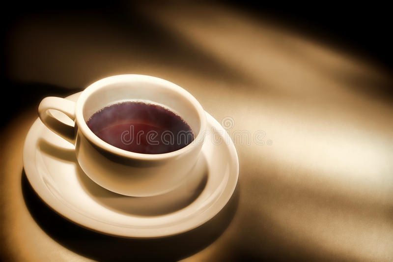 Cup of Light Black Coffee on Coffee Shop Counter. Cup of hot light black coffee with warm steam cloud in a white ceramic mug with saucer on a coffee shop counter royalty free stock photo