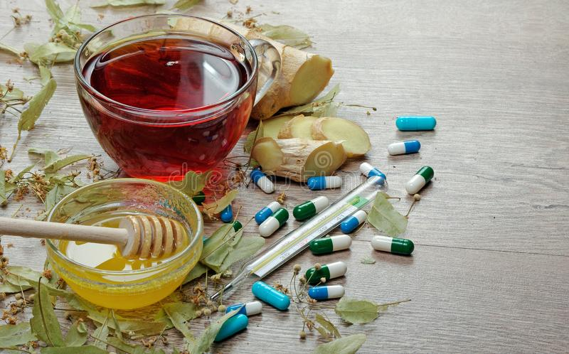 A cup of linden tea, honey, ginger, thermometer and tablets. traditional remedies for colds and flu. Linden tea on wooden table. a cup of linden tea, honey stock photos