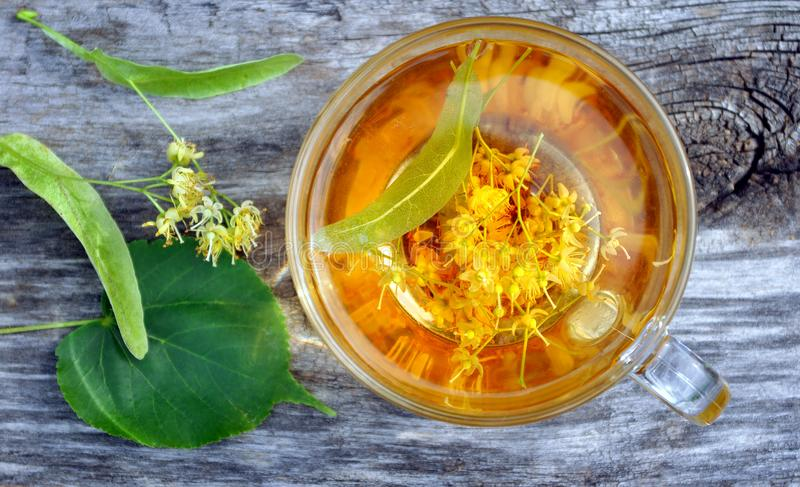 Cup of linden tea on the wooden table. top view. herbal tea. flu and cold remedies. Cup of linden tea on the wooden table. herbal tea. flu and cold remedies royalty free stock photos