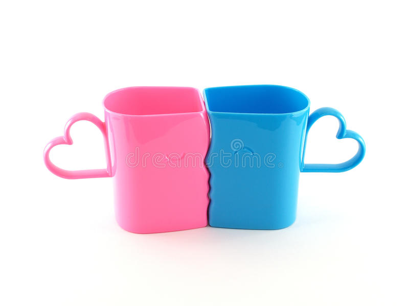 closeup two colorful (pastel pink and blue) plastic cups shaped faces of men and women were kissing with heart shape stock photography