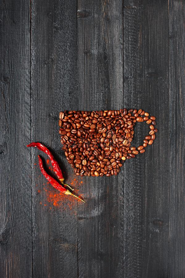 Cup made of coffee beans with chili pepper stock image