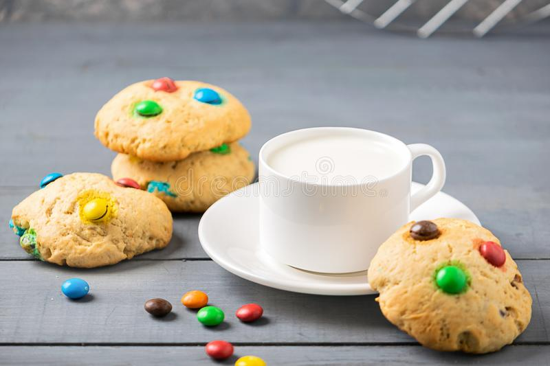 A cup of milk and cookies decorated with colorful jelly beans candies on a gray background. Children`s breakfast snack. A cup of milk and homemade cookies stock images