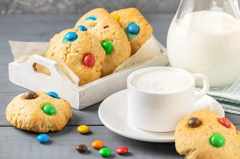 A cup of milk and cookies decorated with colorful jelly beans candies on a gray background. Children`s breakfast snack. A cup of milk and homemade cookies royalty free stock image