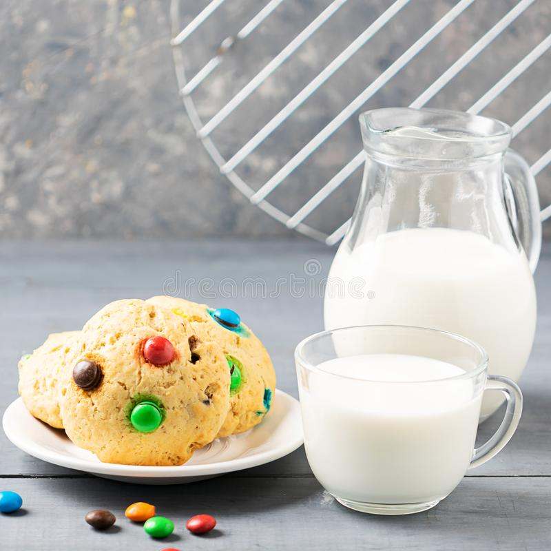 A cup of milk and homemade cookies decorated with colorful jelly beans candies on a gray table background. Copy space. stock image