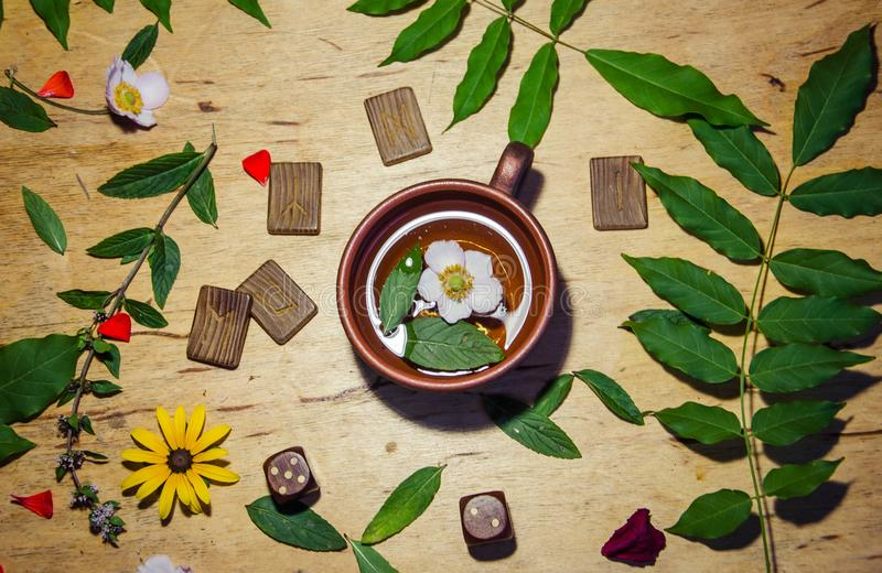 A cup of mint tea and some runes and dice stock photo