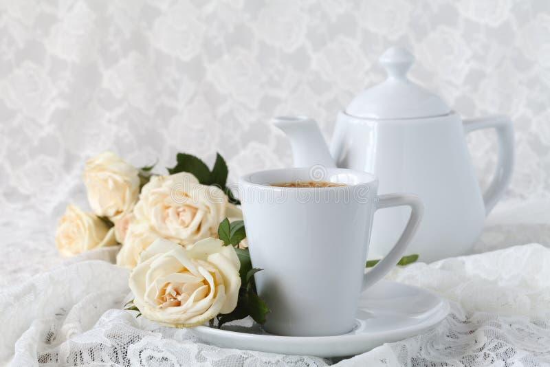 Cup mit einem Saucer Empfindliche Rosen der weißen Blumen lizenzfreie stockfotos