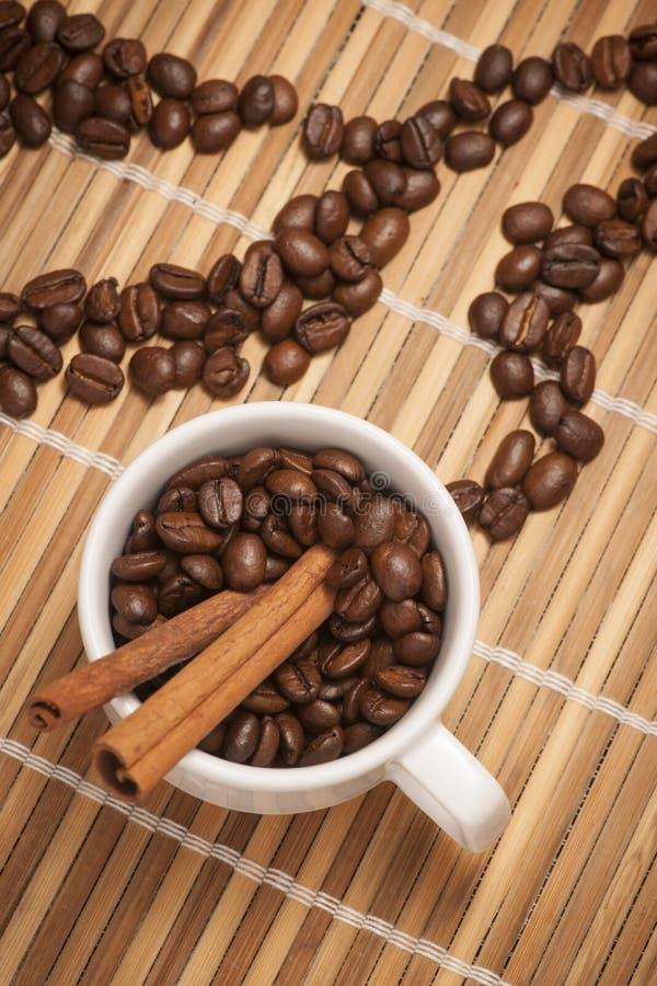 Cup mit Kaffeebohnen und Zimt lizenzfreie stockfotografie