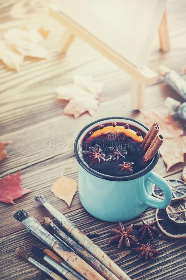 Cup of mulled wine, artist paintbrushes, paints, artistic canvas on easel and autumn leaves. stock photography
