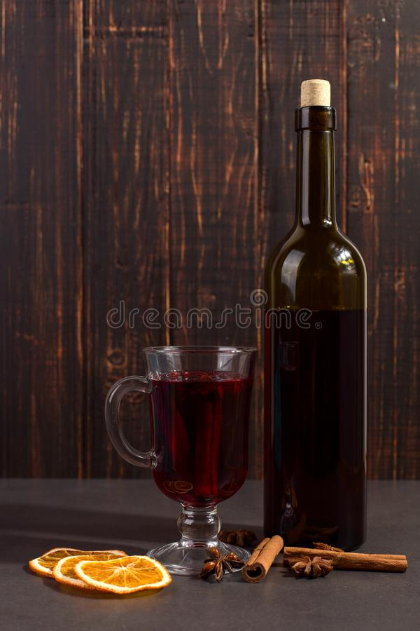 Cup of mulled wine with spices, bottle, dry leaves and oranges on table. Autumn mood, method to keep warm in the cold, copy space. Dark, scarf, blue, hot stock images