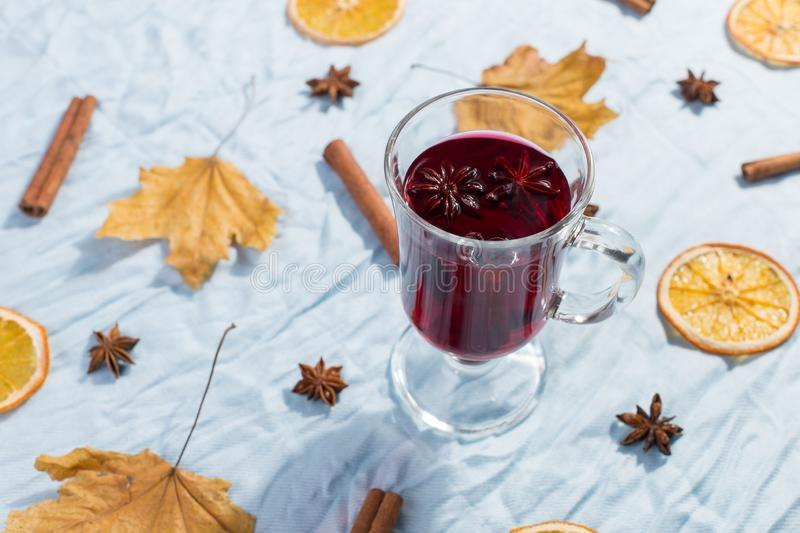 A cup of mulled wine with spices, dry leaves and oranges on the table. Autumn mood, a method to keep warm in the cold, copy space. A cup of mulled wine with stock images