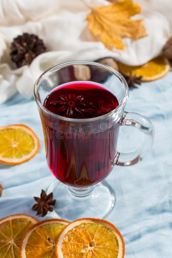 A cup of mulled wine with spices, dry leaves and oranges on the table. Autumn mood, a method to keep warm in the cold, copy space. A cup of mulled wine with stock photos