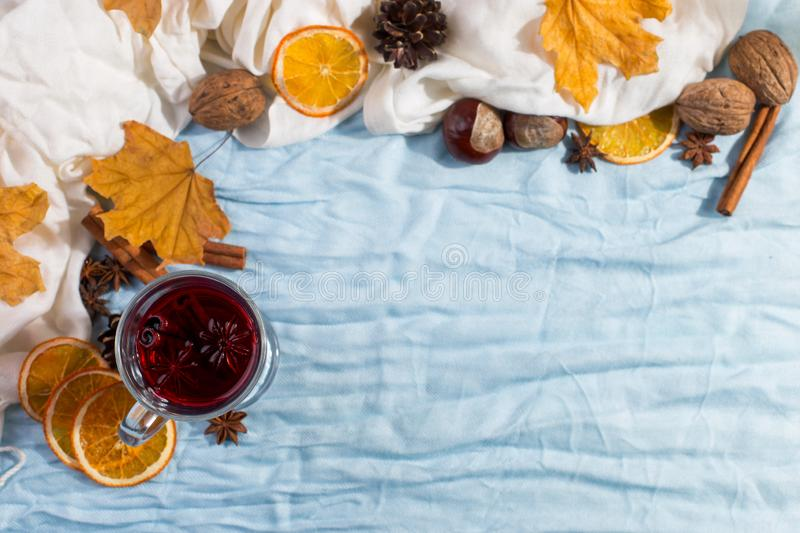 A cup of mulled wine with spices, dry leaves and oranges on the table. Autumn mood, a method to keep warm in the cold, copy space. A cup of mulled wine with royalty free stock image