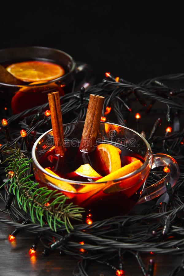 Cup of New Year`s mulled wine with orange and a cinnamon stick with a garland stock image