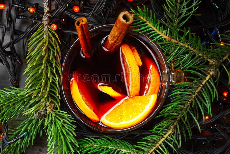 Cup of New Year`s mulled wine with orange and a cinnamon stick with a garland. Flat lay royalty free stock photography