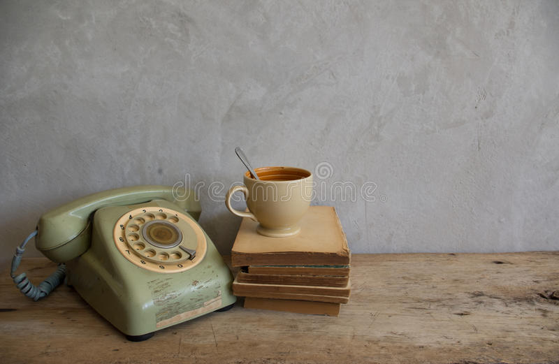 A cup with old book and phone on wood. stock photos