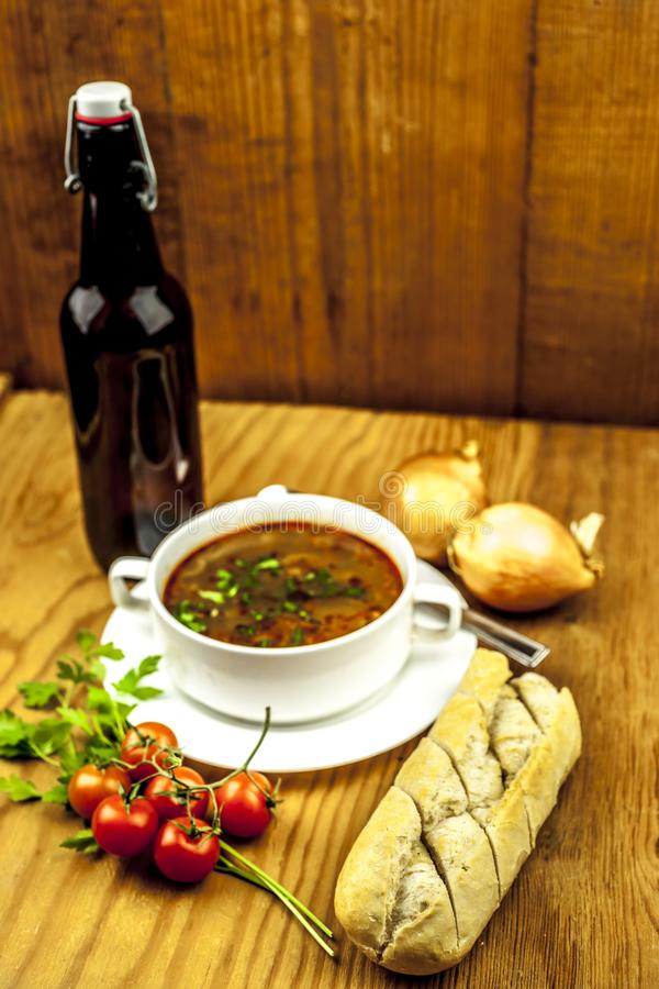 Cup of onion soup with beer and tomatoes, onion and baguette royalty free stock photo