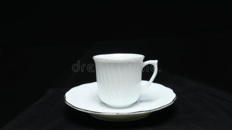 A small, bowl-shaped container for drinking from, typically having a handle. stock image