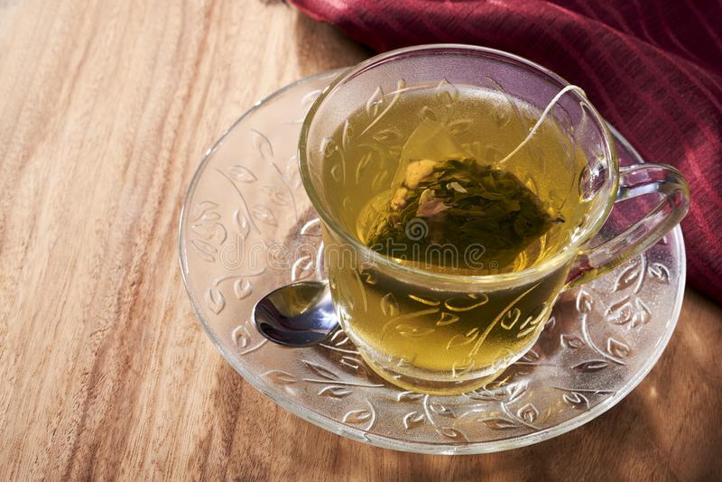 A cup of peach oolong green tea brewed with a tea bag royalty free stock images