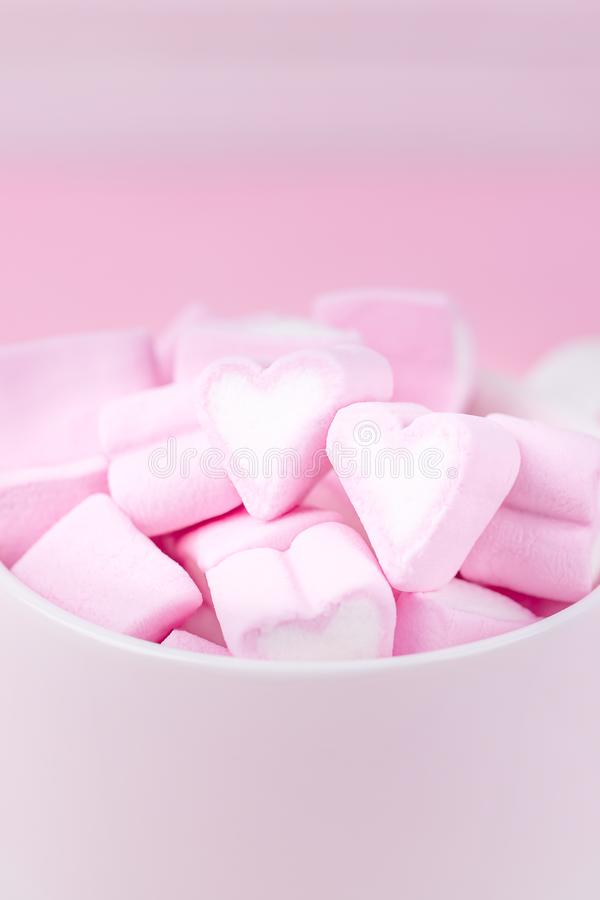 Cup of pink marshmallow hearts on a soft pink background. Valentines day love concept. Copy space royalty free stock image