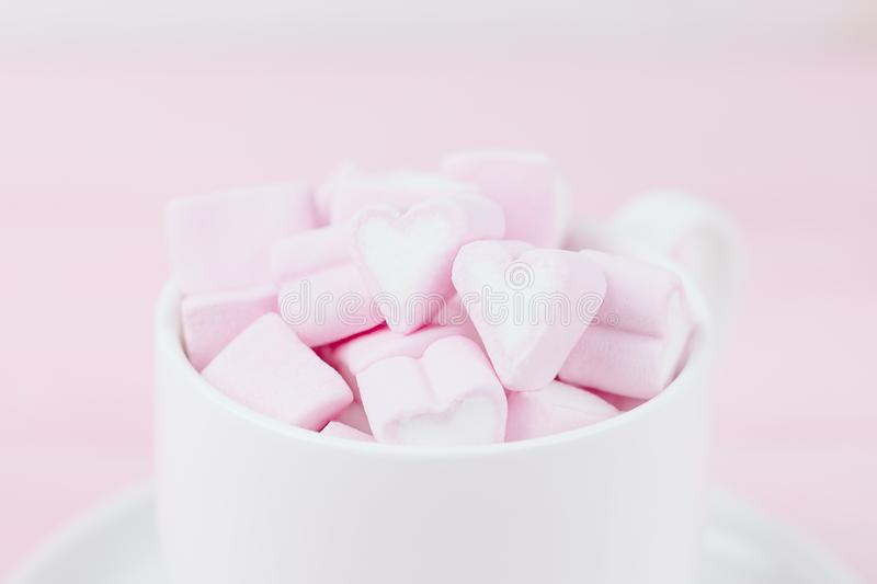 Cup of pink marshmallow hearts on a pink background. Valentines day love concept. Copy space stock photos
