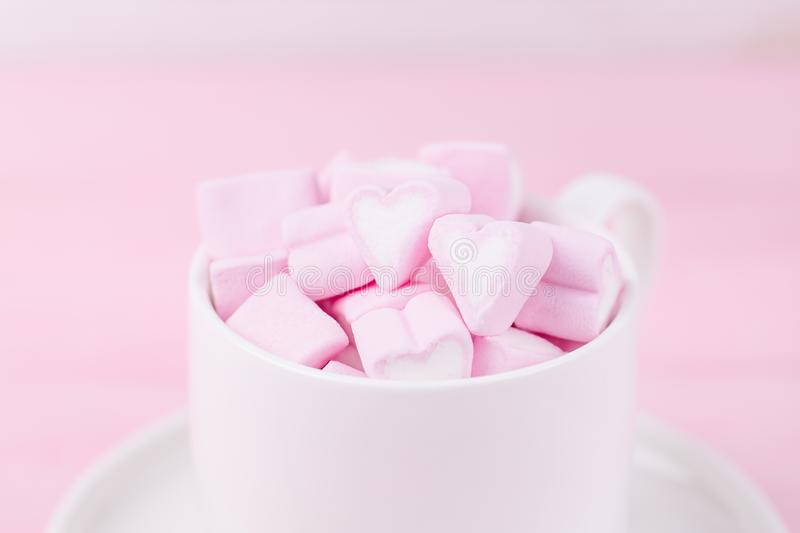 Cup of pink marshmallow hearts on a soft pink background. Valentines day love concept. Cup of pink marshmallow hearts on a soft pink background royalty free stock image