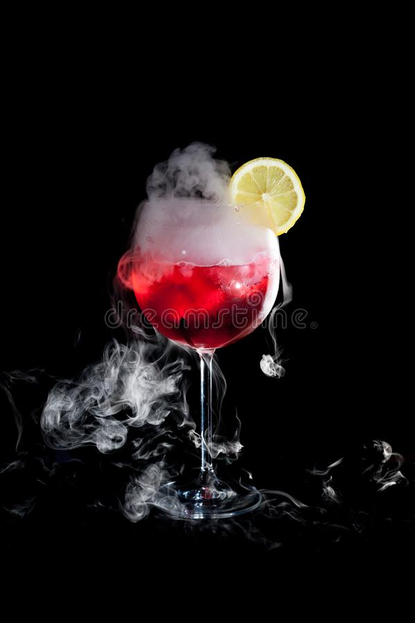 A cup of red cold cocktail with dry ice smoke and a lemon slice royalty free stock photo