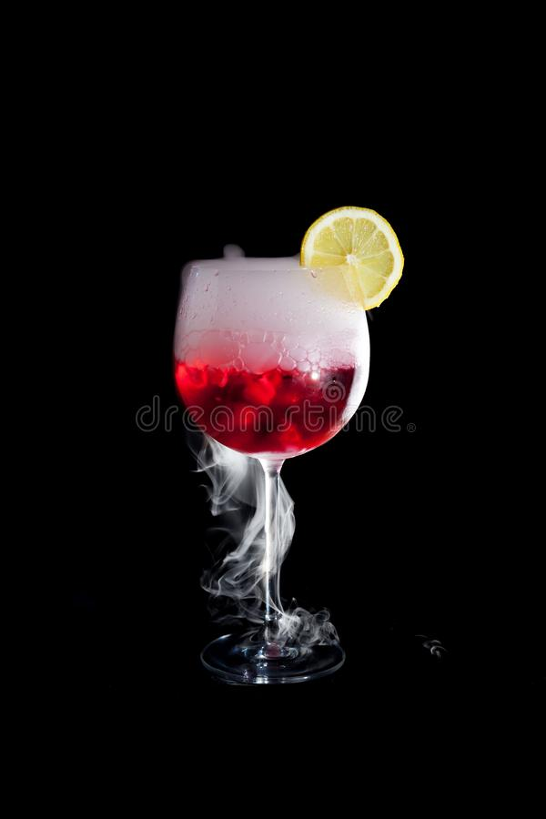 A cup of red cold cocktail with dry ice smoke and a lemon slice. And black background royalty free stock photography
