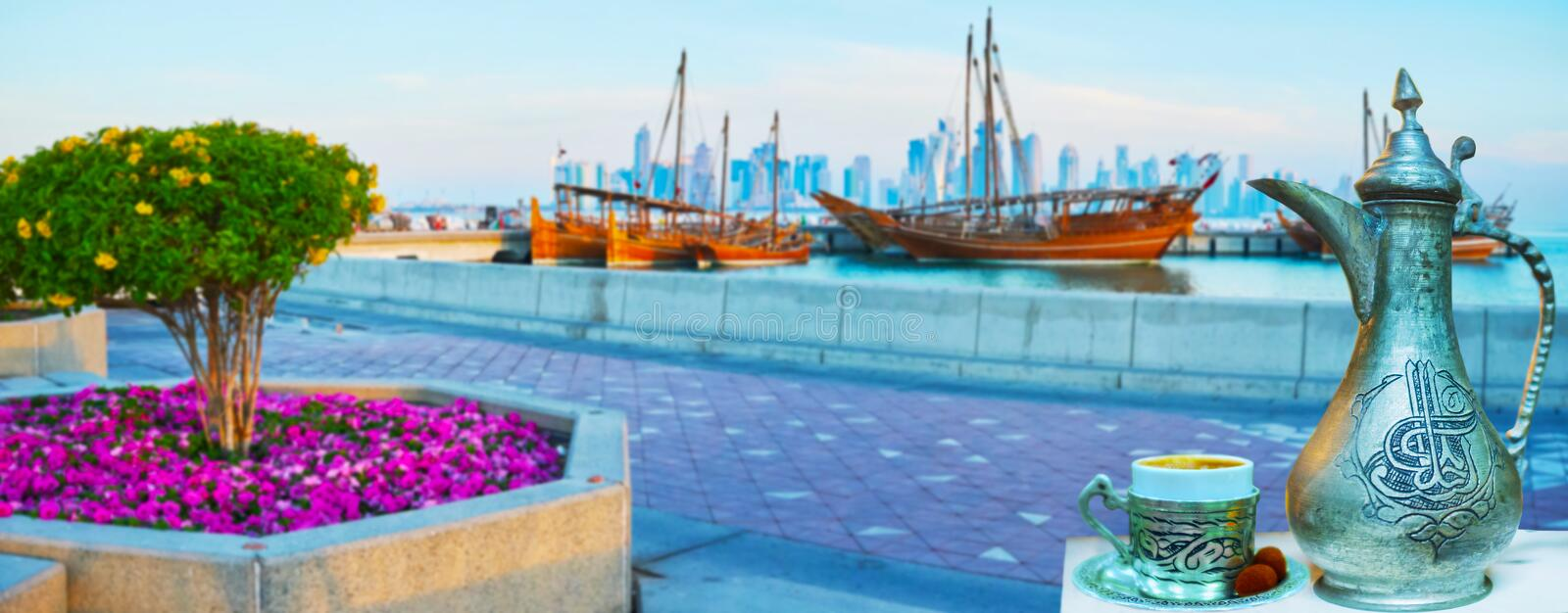 Traditional coffee in Doha harbor, Qatar. A cup of refreshing coffee, brewed in vintage dallah coffeepot, decorated with Islamic patterns, with a view on Doha royalty free stock images