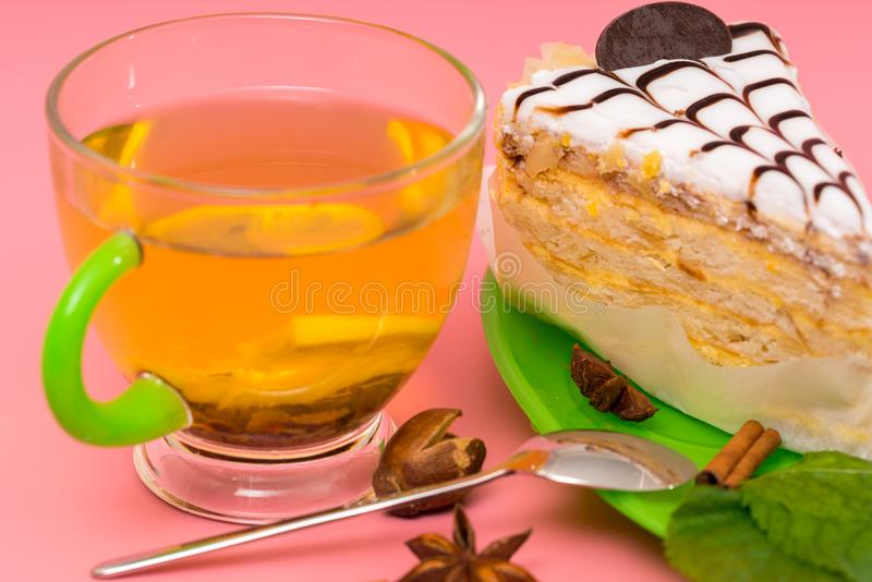 Cup of relaxing spicy lemon tea with layer cake royalty free stock photos
