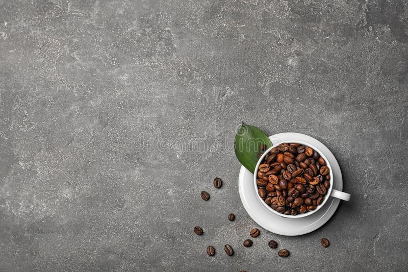 Cup with roasted coffee beans royalty free stock photography