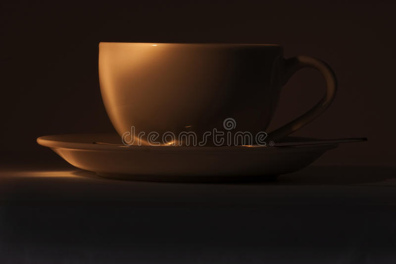 Cup and saucer in dark royalty free stock image