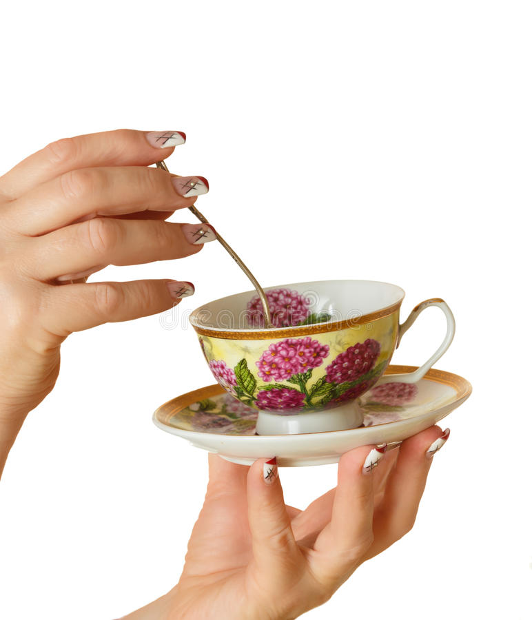 Cup and saucer in his hand with a manicure royalty free stock image