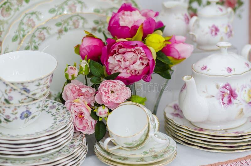 Cup saucer set, plates, teapot and tablecloth stock photos