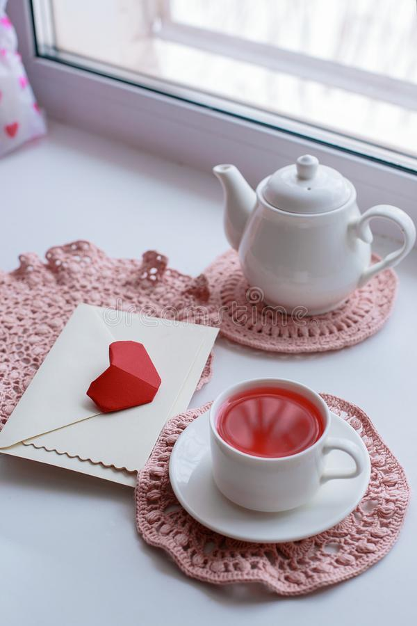 Cup of scented pink tea on crocheting napkin, teapot and envelope on windowsill. Valentines day. Romance Good morning royalty free stock photography