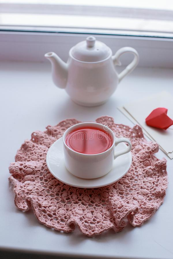 Cup of scented pink tea on crocheting napkin, teapot and envelope on windowsill. Valentines day. Romance Good morning stock image