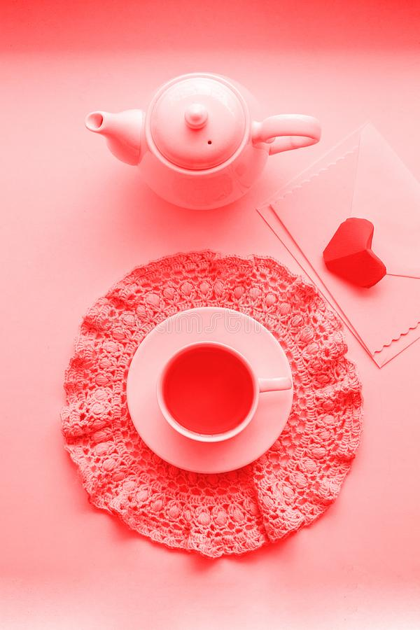 Cup of scented pink tea on crocheting napkin, teapot and envelope on windowsill. Valentines day. Romance Good morning, living royalty free stock photography