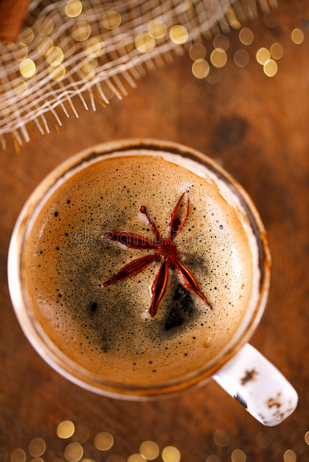 A cup of spiced coffee with anise star and glitter royalty free stock photo