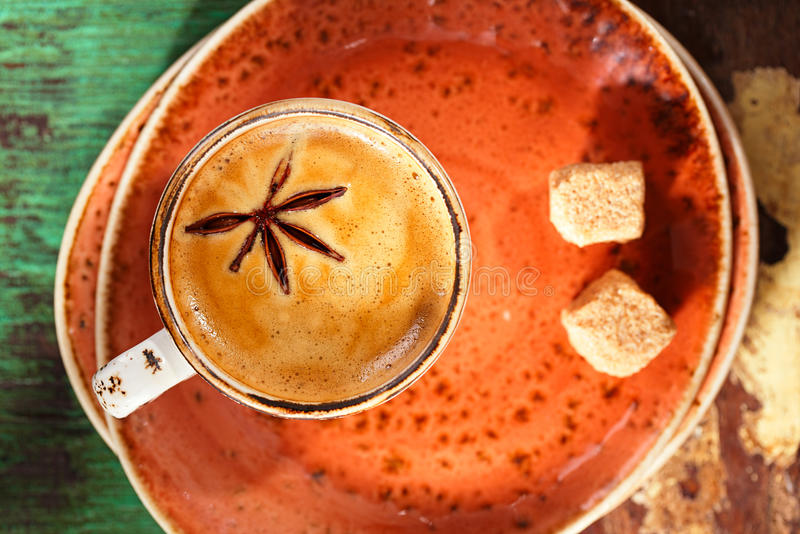 A cup of spiced coffee with anise star and soucers stock photo