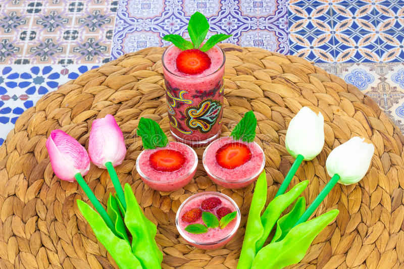 A cup of Strawberry Juice with mint leaves on an Oriental Colorful Background. Cup of Strawberry Juice on an Oriental Colorful Background with Flowers & mint royalty free stock images
